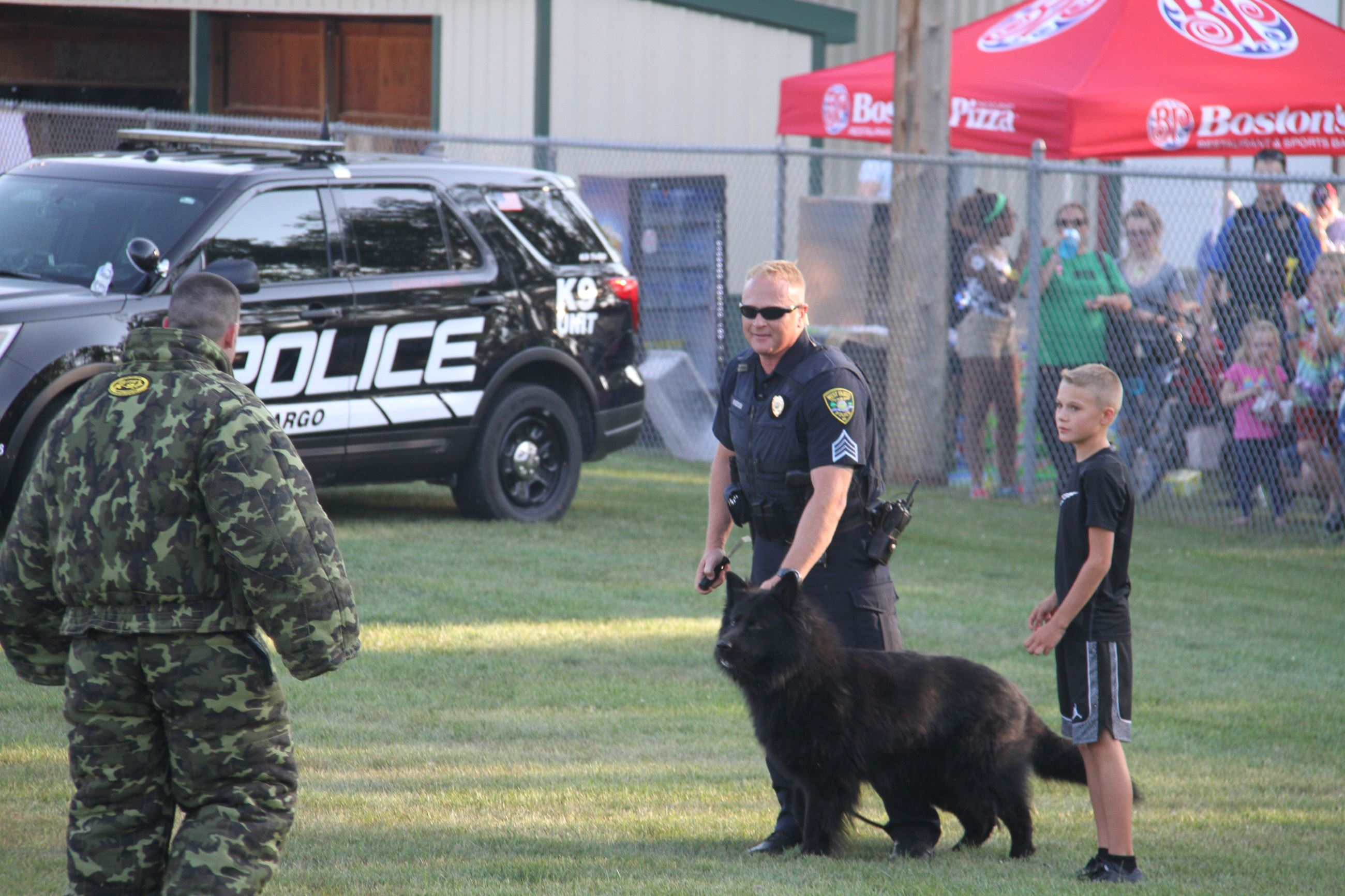 A young West Fargo resident assists Sgt. Nielsen and K9 Disco with a demonstration